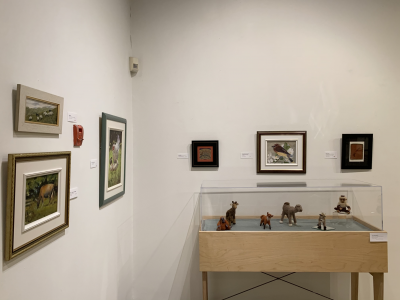 Framed photos of 6 different animals are shown hanging on the wall. There is a small display case against the wall showing small sculptures of another 6 animals