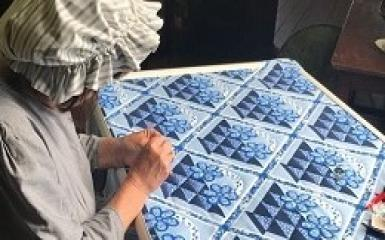 A woman working on a blue quilt